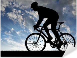 Naklejka Pixerstick Sylwetka rowerzysty na rowerze na drogach na zachodzie słońca
