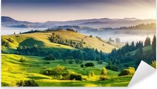 Naklejka Pixerstick Zielone pagórki z górami w oddali