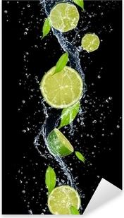 Nálepka Pixerstick Limes ve stříkající vodě, izolovaných na černém pozadí