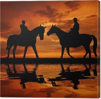Obraz na płótnie Kowboje sylwetka z koni w zachodzie słońca