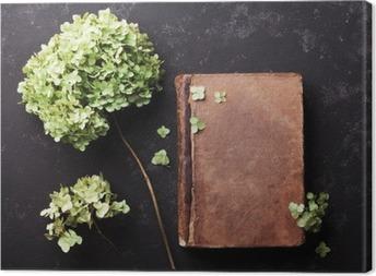Obraz na płótnie Martwa natura z starej książki i suszonych kwiatów hortensji na czarnym rocznika tabeli widoku z góry. Płaski lay stylizacji.