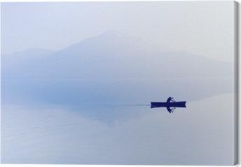 Obraz na płótnie Mgła nad jeziorem. Sylwetka górami w tle. Mężczyzna pływa w łodzi z wiosła.
