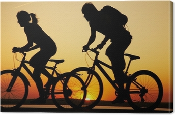 Obraz na płótnie Młoda para na rowerach na zachodzie słońca