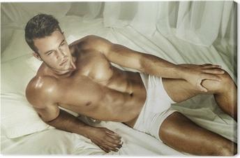 Obraz na płótnie Przystojny nagi mężczyzna leżał w łóżku.