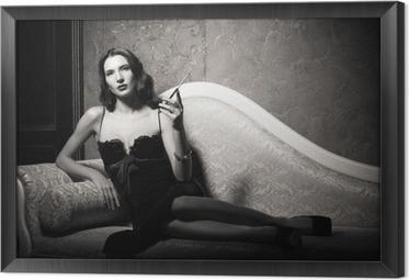 Obraz na płótnie w ramie Film noir stylu: elegancki młoda kobieta, leżąc na kanapie i palenia papierosów. Czarny i biały