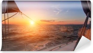 Papier peint autocollant Beau coucher de soleil en pleine mer avec voilier.