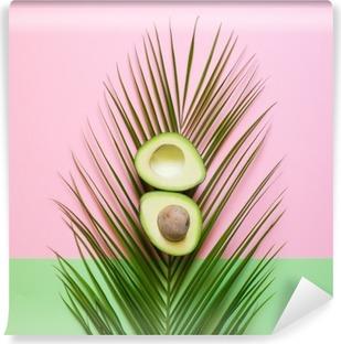 Papier peint vinyle Avocat Ripe sur la feuille de palmier sur un fond coloré. le concept Minimal