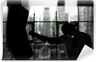 Papier peint vinyle Boxer frappe un sac de boxe contre la fenêtre, la formation
