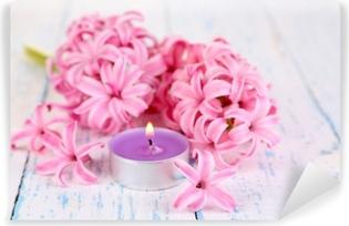 Papier peint vinyle Jacinthe rose avec des bougies sur fond de bois