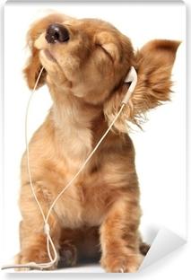 Papier peint vinyle Jeune chiot écoutant de la musique sur un ensemble de tête.