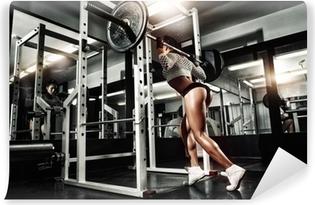 Papier peint vinyle Jeune fille sexy dans la salle de gym faire squat avec  haltères 94817a19b5d