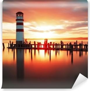 Papier peint vinyle Lever de soleil à la plage avec le phare
