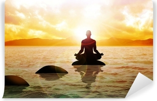 Papier peint vinyle Un chiffre homme méditant sur l'eau calme au lever du soleil