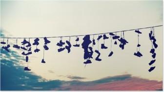 Retro stiliserede silhuetter af sko hængende på kabel ved solnedgang, teenage oprør koncept. Plakat