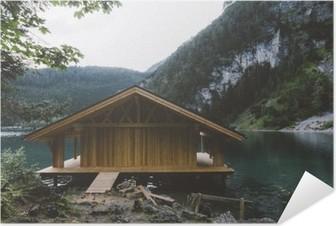 Poster Autoadesivo Casa di legno sul lago con le montagne e gli alberi