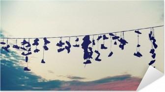 Poster Autoadesivo Retro stilizzata sagome di scarpe appese su cavo al tramonto, adolescente concetto di ribellione.