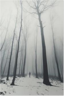 Poster Kışın uzun boylu ağaçlar ormanda adam
