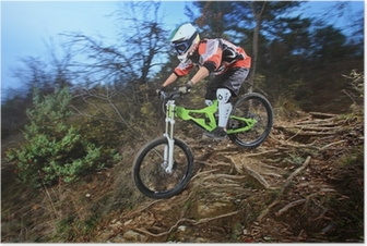 A young man riding a mountain bike downhill style Poster