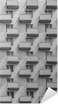 Poster autocollant Un bâtiment avec des balcons et des fenêtres identiques avec une ombre sur le mur