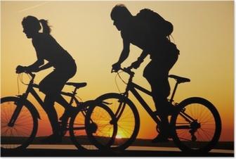Poster Jeune couple bicyclette au coucher du soleil.