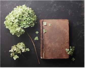 Poster Nature morte avec le vieux livre et fleurs séchées hortensia sur noir table vintage vue de dessus. Appartement style laïque.