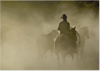 Single Cowboy with rope and horses in the dust Poster