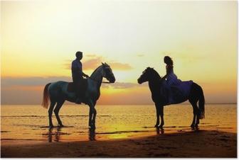 Poster Twee ruiters te paard bij zonsondergang op het strand. Lovers rijden hors