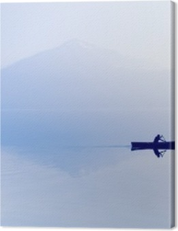 Fog over the lake. Silhouette of mountains in the background. The man floats in a boat with a paddle. Premium prints
