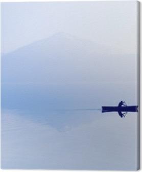 Premiumbilder Dimma över sjön. Siluett av bergen i bakgrunden. Mannen flyter i en båt med en paddel.