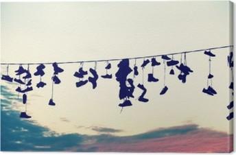 Quadro su Tela Retro stilizzata sagome di scarpe appese su cavo al tramonto, adolescente concetto di ribellione.