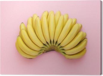 Quadro su Tela Vista dall'alto di banane mature su uno sfondo rosa brillante. stile minimal.