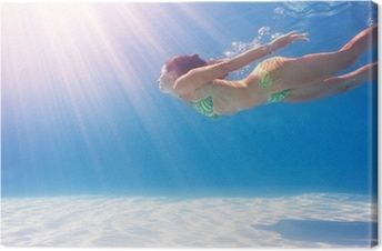 Quadro em Tela Woman swimming underwater in a blue pool.