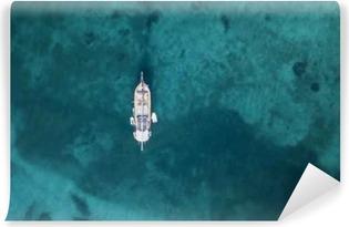 Selbstklebende Fototapete Luftaufnahme einer kleinen Yacht am wunderschönen Strand mit türkisfarbenem und durchsichtigem Meer. Smaragdküste, Sardinien, Italien.