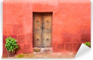Selbstklebende Fototapete Rote Wand und alte Holztür. Architektur in Arequipa, Peru