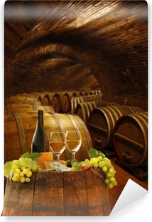 Selbstklebende Fototapete Weinkeller mit Gläsern Weißwein gegen Fässer