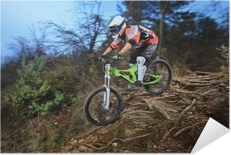 Selbstklebendes Poster Ein junger Mann mit Mountainbike Downhill-Stil