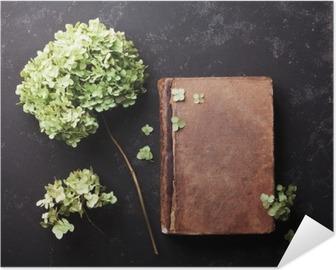 Selbstklebendes Poster Stillleben mit alten Buch und getrockneten Blumen Hortensie auf schwarzem Vintage Tisch Draufsicht. Wohnung lag Styling.