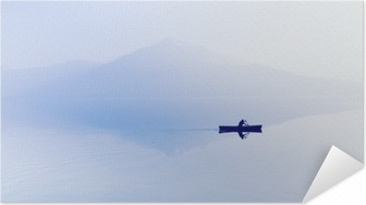 Fog over the lake. Silhouette of mountains in the background. The man floats in a boat with a paddle. Self-Adhesive Poster