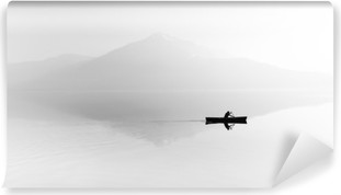 Fog over the lake. Silhouette of mountains in the background. The man floats in a boat with a paddle. Black and white Self-Adhesive Wall Mural