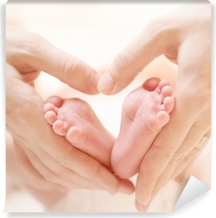 Tiny Newborn Baby's feet on female Heart Shaped hands closeup Self-Adhesive Wall Mural