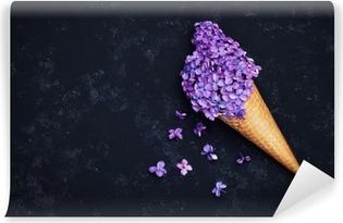 Selvklebende fototapet Is av lilla blomster i vaffelkegle på svart bakgrunn fra oven, vakkert blomsterarrangement, vintagefarge, flat lay styling