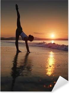 A woman doing a yoga workout at the beach during a sunrise Pixerstick Sticker