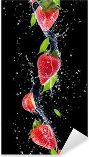 Pixerstick Sticker Aardbeien in het water splash, geïsoleerd op zwarte achtergrond