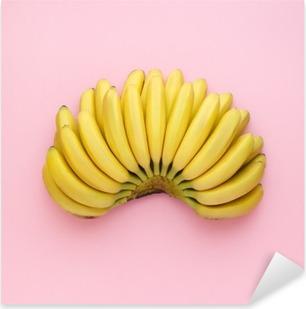 Pixerstick Sticker Bovenaanzicht van rijpe bananen op een heldere roze achtergrond. Minimalistische stijl.
