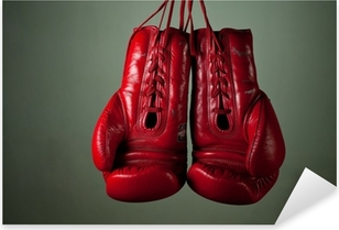Boxing gloves hanging from laces on a grey background Pixerstick Sticker