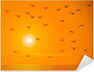 Flying birds against orange sunset. Pixerstick Sticker