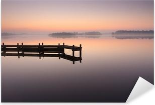 Pixerstick Sticker Jetty tijdens een rustige, mistige zonsopgang op een meer.