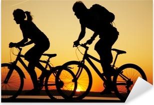 Sticker Pixerstick Jeune couple bicyclette au coucher du soleil.