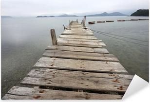 Pixerstick Sticker Kijkt uit over een desolate peer en een boot.
