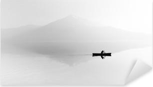 Pixerstick Sticker Mist over het meer. Silhouet van de bergen op de achtergrond. De man drijft in een boot met een peddel. Zwart en wit
